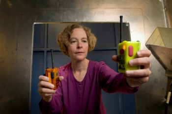 NIST engineer Kate Remley holds two Personal Alert Safety System (PASS) devices with wireless alarm capability. Photo copyright: Paul Trantow/Altitude Arts
