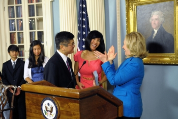 Secretary Clinton applauds Gary Locke as his wife and children look on