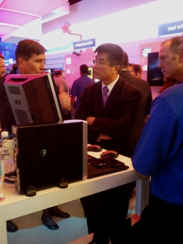 Locke at booth inspecting new devices and equipment