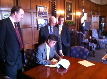 Locke signs document while others look on