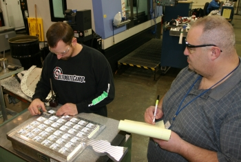 "NIST's Brian Yanick (left) and Jay Brandenburg inspect the Magna Carta platform's rear side after machining.  The special ""nest"" for the wax seal is the keyhole-shaped object at the bottom center."