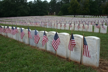 NPS/Andersonville National Historic Site. Flags decorate the graves in Section E of the Andersonville National Cemetery