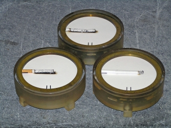 "Examples of results of the Standard Test Method for Measuring the Ignition Strength of Cigarettes (ASTM E2187) are shown. Non-filter (top) and filter (left) cigarettes ""failed,"" having burned the full length in the test. The cigarette that extinguished before burning its full length (right) passed. The test calls for performing 40 such determinations for each cigarette and reporting the number of full-length burns. Cigarettes are positioned on the standard ASTM E2187 test substrate."