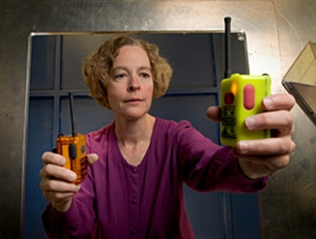 NIST engineer Kate Remley holds two Personal Alert Safety System (PASS) devices with wireless alarm capability (Photo copyright Paul Trantow/Altitude Arts)