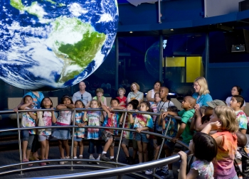 Students and teachers explore global data visualizations with NOAA's Science On a Sphere at the Chicago Museum of Science and Industry (MSI).  The sphere will serve as a focal point for K-12 teacher professional development programs at MSI, which is one of eight new recipients of NOAA Environmental Literacy Grants.  (Photo credit:  MSI)