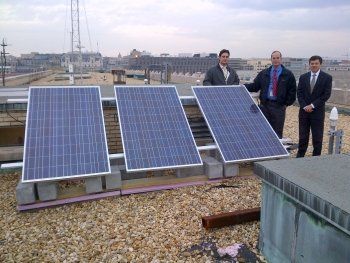 Officials atop the HCHB in Washington with solar panels