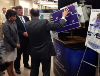 Ball Aerospace President Strain and Commerce Secretary Pritzker view a model of the nation's next polar-orbiting weather satellite.