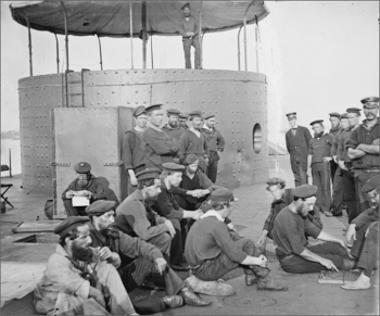 USS Monitor with sailors standing on board