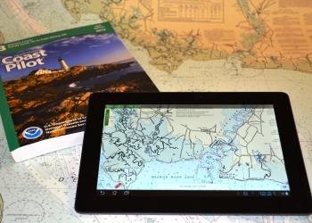 Image of U.S. Coast Pilot guidebook and tablet displaying nautical map