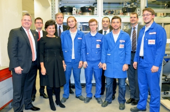 Secretary Pritzker poses with members of iwis Motorsystems after a tour of the facilities