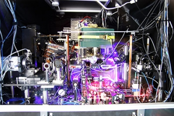 JILA's experimental atomic clock based on strontium atoms held in a lattice of laser light is the world's most precise and stable atomic clock. The image is a composite of many photos taken with long exposure times and other techniques to make the lasers more visible. Credit: Ye group and Baxley/JILA
