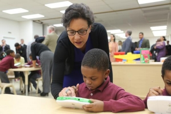 Commerce Secretary Penny Pritzker and a student at the Langdon Education Campus explore a LeapFrog handheld device, the 700,000th design patent awarded by the United States Patent and Trademark Office