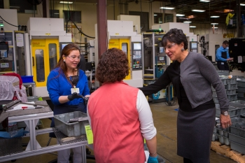 Secretary Pritzker talks with employees of the Leatherman Tool Group, Inc during a tour