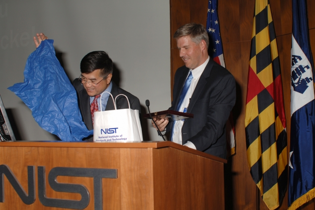 Secretary Locke receiving a message of thanks written on the head of a pin using nanotechnology.