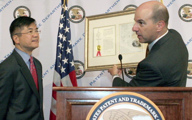 Under Secretary of Commerce for Intellectual Property and Director of the United States Patent Office (USPTO) David Kappos presents Commerce Secretary Gary Locke with a faux patent certificate during Locke's visit to the USPTO