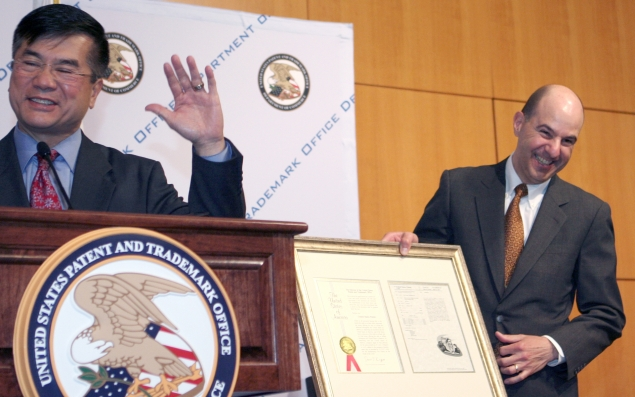 Secretary Locke and USPTO Director Kappos share a laugh over a faux patent certificate presented to the Secretary during his visit there to thank employees for their hard work in reducing the patent backlog.