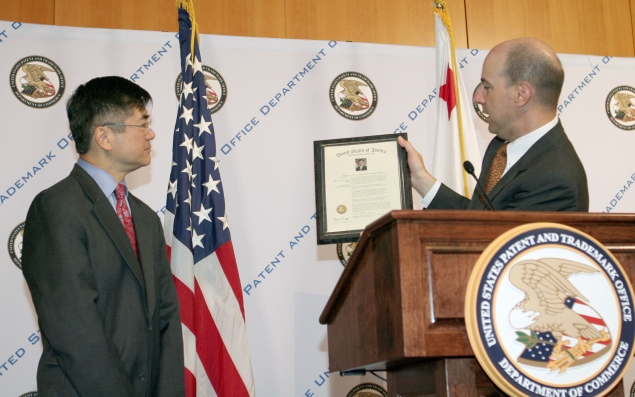 Under Secretary of Commerce for Intellectual Property and Director of the United States Patent Office (USPTO) David Kappos presents Commerce Secretary Gary Locke with a faux trademark certificate during Locke's visit to the USPTO on June 22