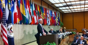 Bryson flanked by flags at the State Department