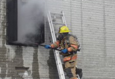 Image of a firefighter on ladder with building smoke.