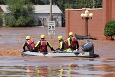 Image of rescuers in boat on flooded city street. Click for larger image.
