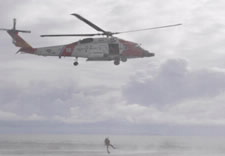 Image of helicopter with responder hovering over water rescuing a victim. Click for larger image.