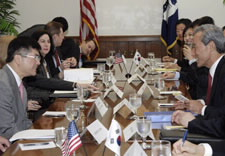 Locke and Kim at conference table with aides. Click for larger image.