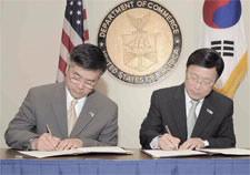 Secretary Locke and Minister Lee are pictured signing document with U.S. and South Korean flags in background. Click for larger image.
