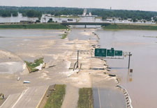 Image of washed-out highway by flood waters. Click for larger image.