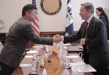 Locke and Uribe shake hands across the conference table. Click for larger image.