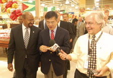 Image of Mayor Nutter, Secretary Locke and reporter with microphone in store. Click for larger image.