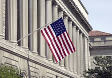 Image of flag flying from facade of U.S. Department of Commerce's Herbert Clark Hoover Building
