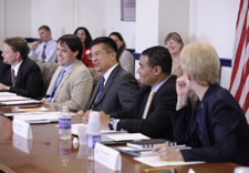 Secretary Locke seated at table with Board  participants. Click for larger image.