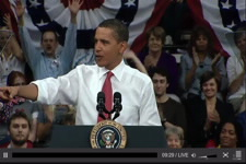 Screen capture image of White House video showing Obama with students and faculty behind him.