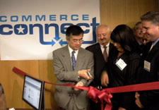 Locke with scissors cutting ribbon at ceremony. Click for larger image.