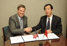 NIST Deputy Director Patrick Gallagher and Yin Chaomin, the vice administrator of the Chinese Earthquake Administration, shaking hands while seated at signing table.