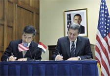 Locke and Rachid seen signing document. Click for larrger image.