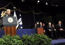 Biden speaking on podium with award winners seated behind. Click for larger image.