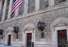 U.S. Department of Commerce Fourteenth Street main entrance with holiday wreaths and bows above doors. Click for larger image.
