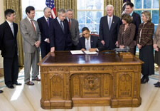 Secretary Locke at far left watches as President Obama signs Act. Click for larger image.