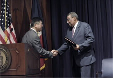 Locke and Delatour on stage shaking hands. Click for larger image.