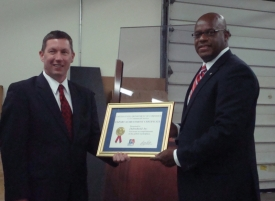 Photo of Maffei and Wade holding framed certificate