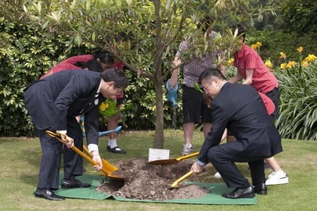 Secretary Locke plants tree using composted hotel waste.